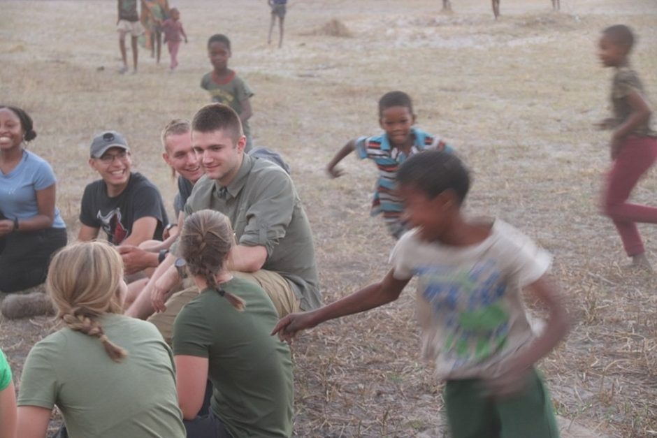 cadet plays with children in Botswana
