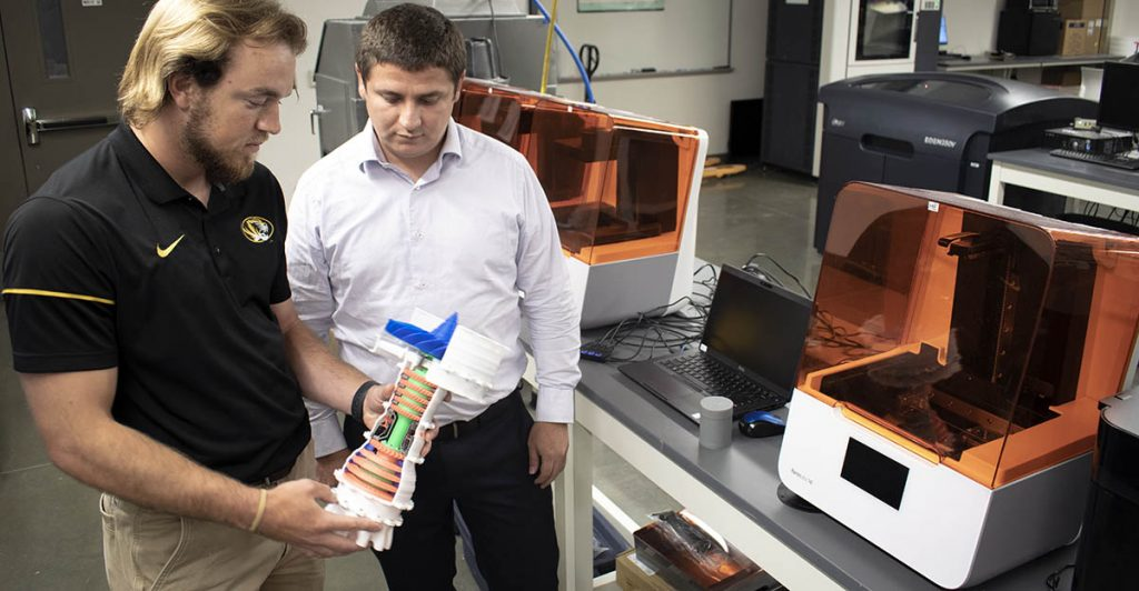 Two men look at 3D printed object in lab.