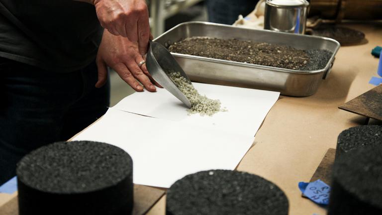 Hands working with plastic asphalt mixture.
