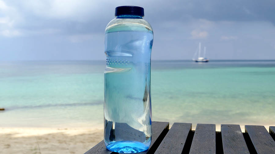 Bottle of water on table in front of ocean.